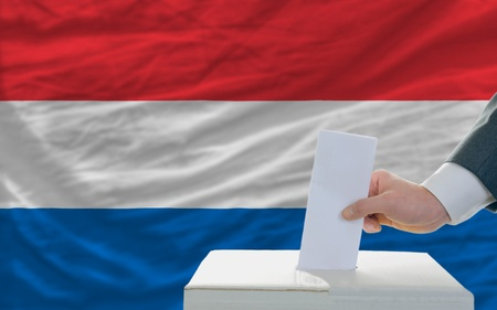man putting ballot in a box during elections in netherlands in fornt of flag photo