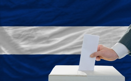 man putting ballot in a box during elections in nicaragua in front of flag photo