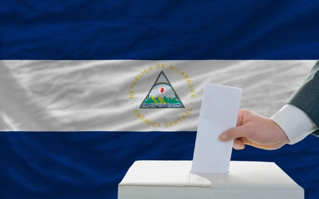 parliamentary: man putting ballot in a box during elections in nicaragua in front of flag