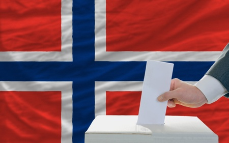 man putting ballot in a box during elections in norway in front of flag photo