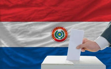 man putting ballot in a box during elections in paraguay in front of flag photo