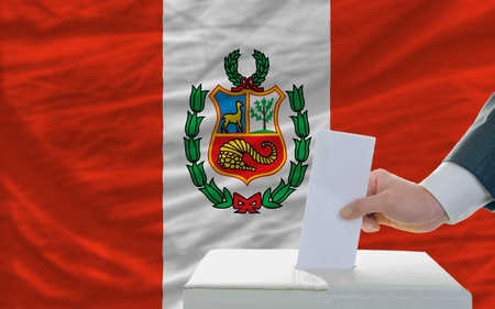 man putting ballot in a box during elections in peru in front of flag photo