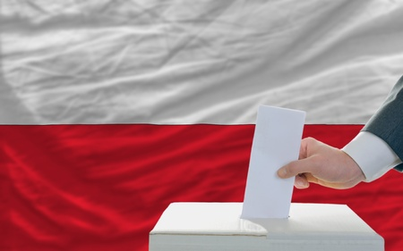 man putting ballot in a box during elections in poland in front of flag