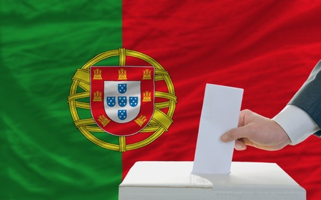 man putting ballot in a box during elections in portugal in front of flag photo
