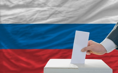 man putting ballot in a box during elections in russia in front of flag photo
