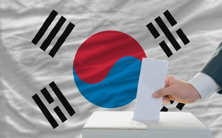 man putting ballot in a box during elections in south korea in front of flag photo