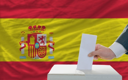 electorate: man putting ballot in a box during elections in spain in front of flag