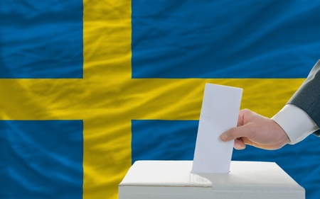 man putting ballot in a box during elections in sweden in front of flag photo