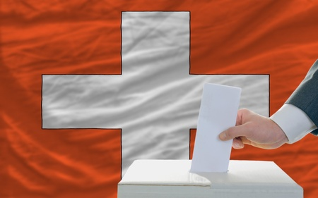 man putting ballot in a box during elections in swiss in front of flag