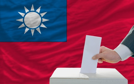 man putting ballot in a box during elections in taiwan in front of flag photo