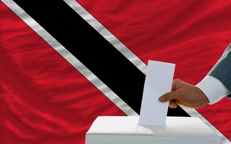 man putting ballot in a box during elections in trinidad tobago in front of flag photo