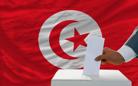man putting ballot in a box during elections in tunisia in front of flag photo