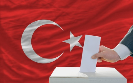 man putting ballot in a box during elections in turkey in front of flag photo