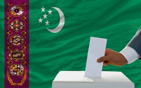 man putting ballot in a box during elections in turkmenistan in front of flag photo