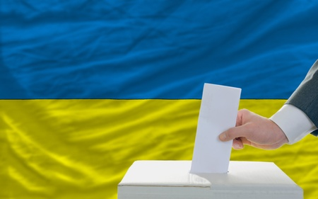 man putting ballot in a box during elections in ukraine in front of flag Stock Photo - 11493677