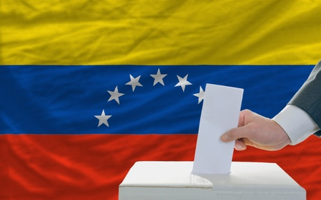 man putting ballot in a box during elections in venezuela in front of flag Stock Photo - 11493906