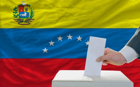 man putting ballot in a box during elections in venezuela in front of flag photo