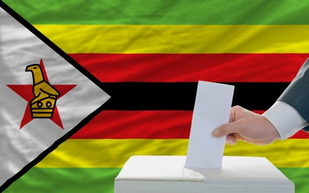 man putting ballot in a box during elections in zimbabwe in front of flag photo