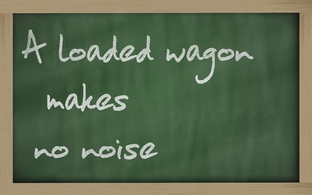 wriiting: Blackboard writings A loaded wagon makes no noise Stock Photo