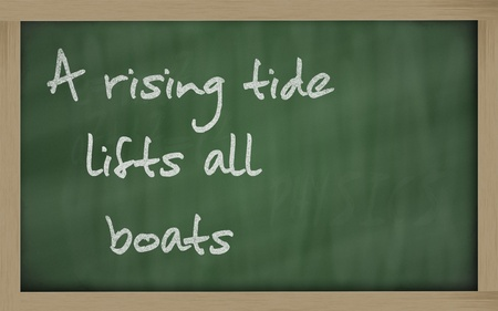 Blackboard writings A rising tide lifts all boats Stock Photo
