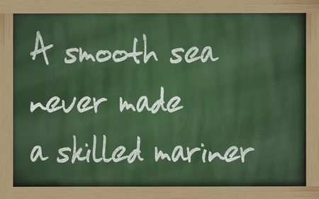 wriiting: Blackboard writings A smooth sea never made a skilled mariner  Stock Photo