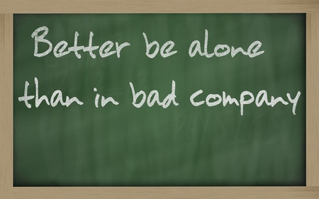 than: Blackboard writings Better be alone than in bad company  Stock Photo
