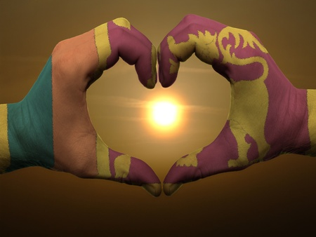 sri lankan flag: Gesture made by srilanka flag colored hands showing symbol of heart and love during sunrise Stock Photo