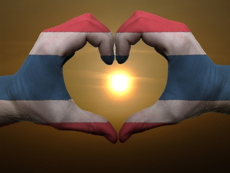 Gesture made by thailand flag colored hands showing symbol of heart and love during sunrise photo