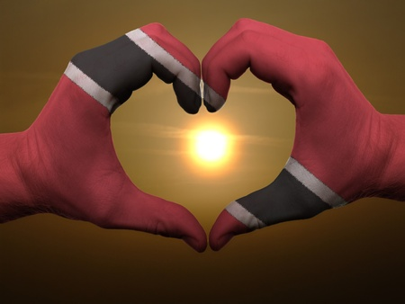 Gesture made by trinidad tobago flag colored hands showing symbol of heart and love during sunrise