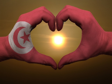 Gesture made by tunisia flag colored hands showing symbol of heart and love during sunrise photo