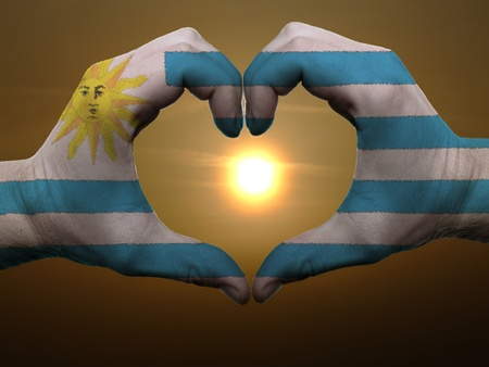 Gesture made by uruguay flag colored hands showing symbol of heart and love during sunrise photo