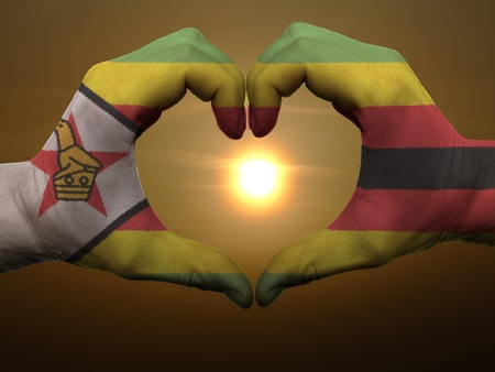 Gesture made by zimbabwe flag colored hands showing symbol of heart and love during sunrise photo