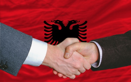 albanian: two businessmen shaking hands after good business investment  agreement in albania, in front of flag