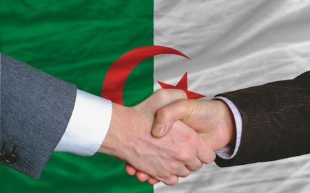 entrepeneur: two businessmen shaking hands after good business investment  agreement in algeria, in front of flag