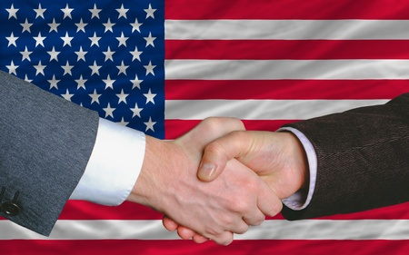 syndicate: two businessmen shaking hands after good business investment  agreement in america, in front of flag