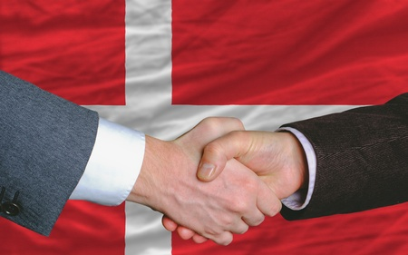 syndicate: two businessmen shaking hands after good business investment  agreement in denmark, in front of flag Stock Photo