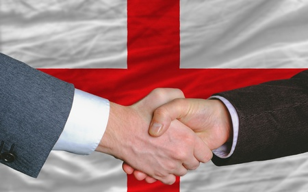 two businessmen shaking hands after good business investment  agreement in england, in front of flag Stock Photo - 11494524