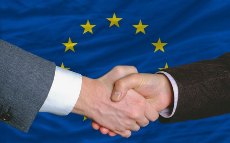two businessmen shaking hands after good business investment  agreement in europe, in front of flag Stock Photo