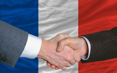 two businessmen shaking hands after good business investment  agreement in iceland, in front of flag photo