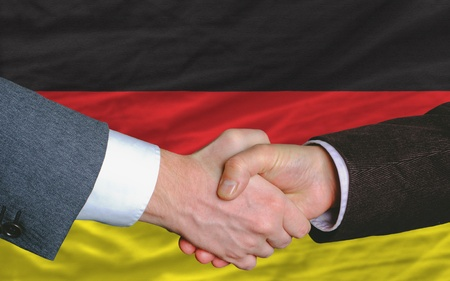 syndicate: two businessmen shaking hands after good business investment  agreement in germany, in front of flag Stock Photo