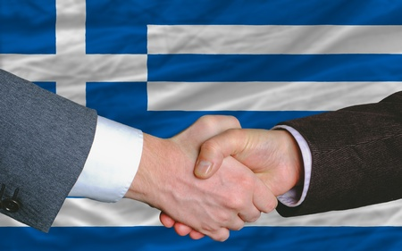 two businessmen shaking hands after good business investment  agreement in greece, in front of flag photo