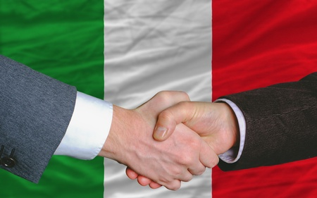 syndicate: two businessmen shaking hands after good business investment  agreement in italy, in front of flag