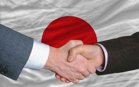 日本では、フラグの前に良いビジネス投資協定後に握手 2 人のビジネスマン