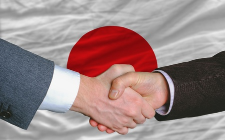 business concern: two businessmen shaking hands after good business investment  agreement in japan, in front of flag