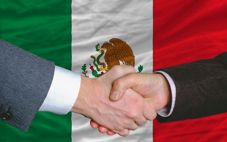two businessmen shaking hands after good business investment  agreement in mexico, in front of flag photo