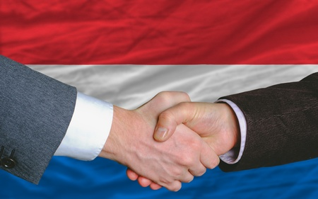 two businessmen shaking hands after good business investment  agreement in holland, in front of flag photo