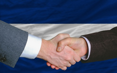 two businessmen shaking hands after good business investment  agreement in nicaragua, in front of flag photo