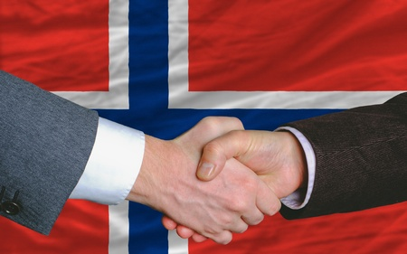entrepeneur: two businessmen shaking hands after good business investment  agreement in norway, in front of flag