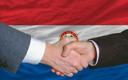 entrepeneur: two businessmen shaking hands after good business investment  agreement in paraguay, in front of flag