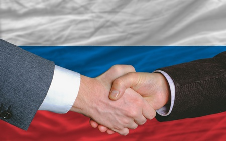 two businessmen shaking hands after good business investment  agreement in russia, in front of flag Stock Photo